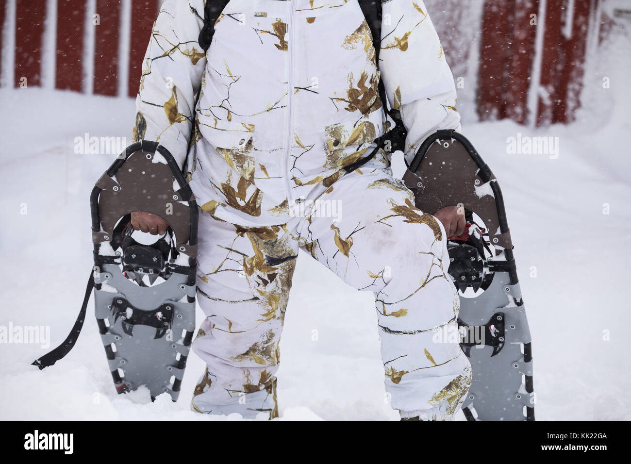 Winter snowshoeing. Man dressed in winter camo clothing, holding snowshoes outside his red cabin in the snow, when - Stock Image