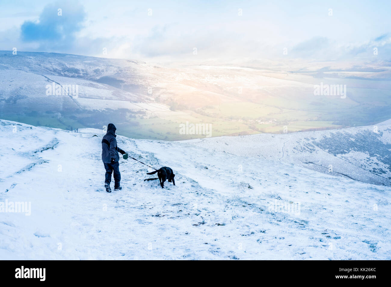 Dog walking in the snow. Hiker and dog out walking in the late Autumn snow on The Great Ridge, Derbyshire, Peak - Stock Image
