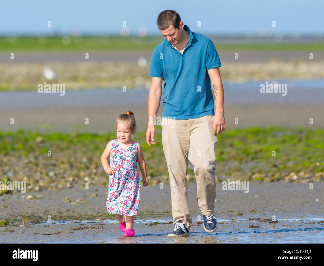 Young girl walking with a man on a beach. - Stock Image