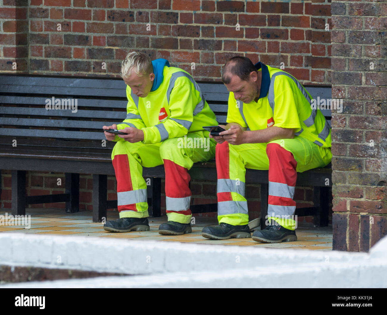 Pair of male workmen sitting taking a break while using mobile phones. - Stock Image