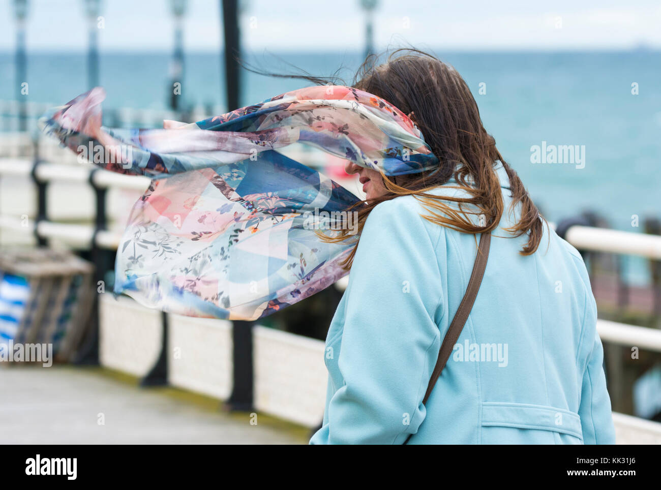 Woman walking on a windy day in Autumn with a coat and scarf, blowing in the wind, in the UK. - Stock Image