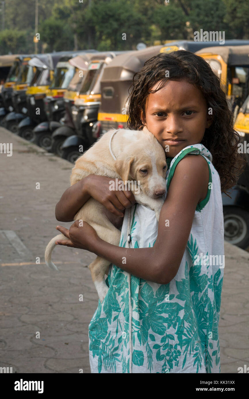 Young Indian girl holds pet puppy dog - Stock Image