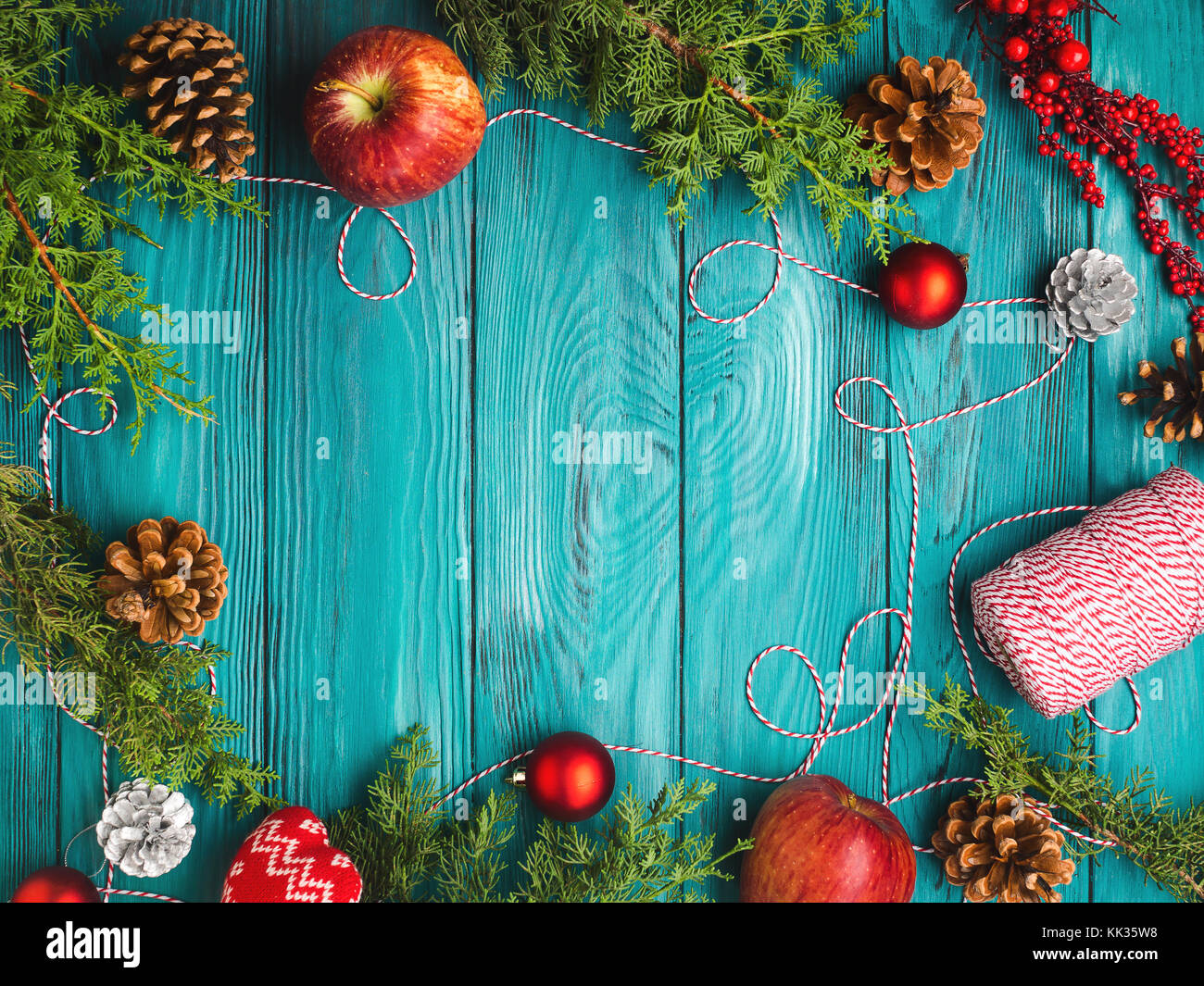 Christmas dark green frame background with pine cones, red baubles and twine, apples. Wooden table texture - Stock Image