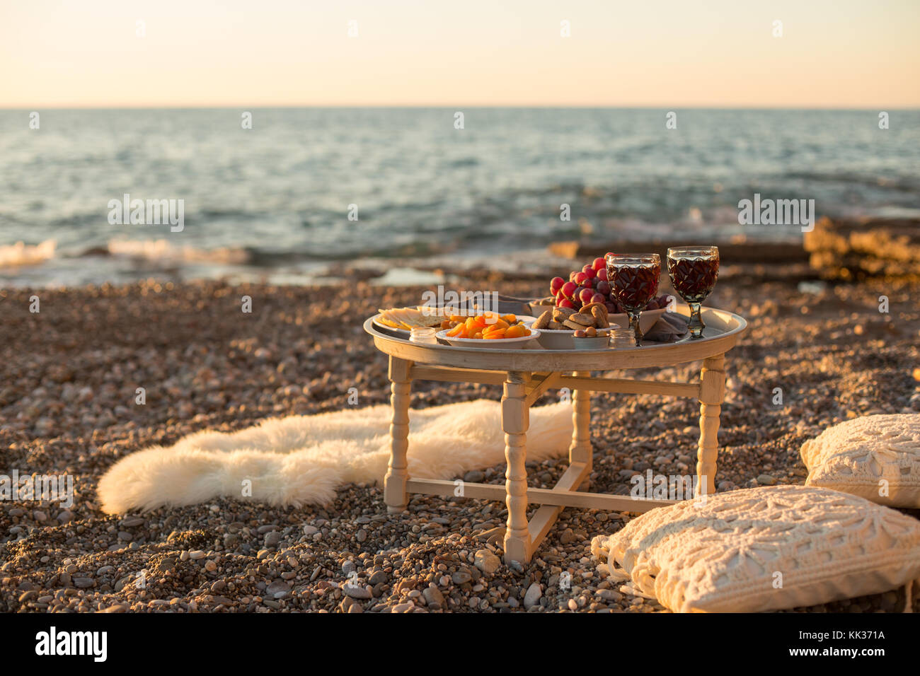 Romantic Outdoor Dinner With Wine And Cheese By Seaside. Two Glasses Of  Wine, Grapes, Dried Fruits And Cheese Placed On Small Round Table, With  White