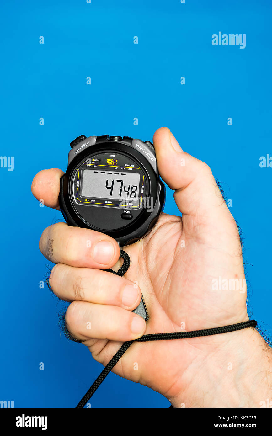 hand of coach with a stopwatch over a blue background - Stock Image