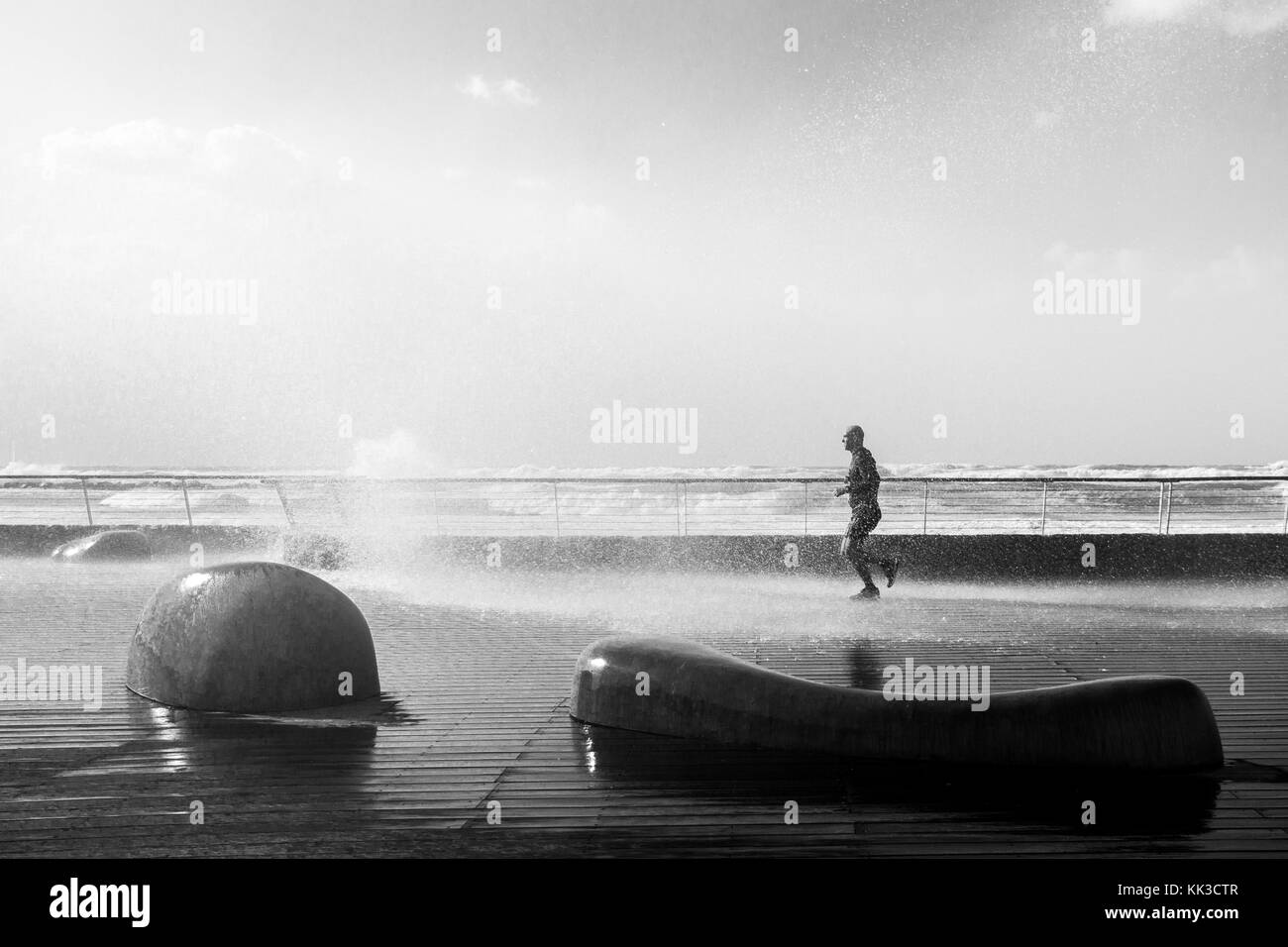 Runner gets splashed by a large wave at Tel Aviv Port, Israel - Stock Image