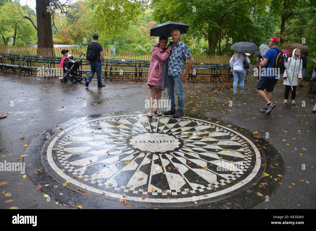 Tourists and fans pose by Strawberry Fields mosaic memorial in Central Park - Stock Image
