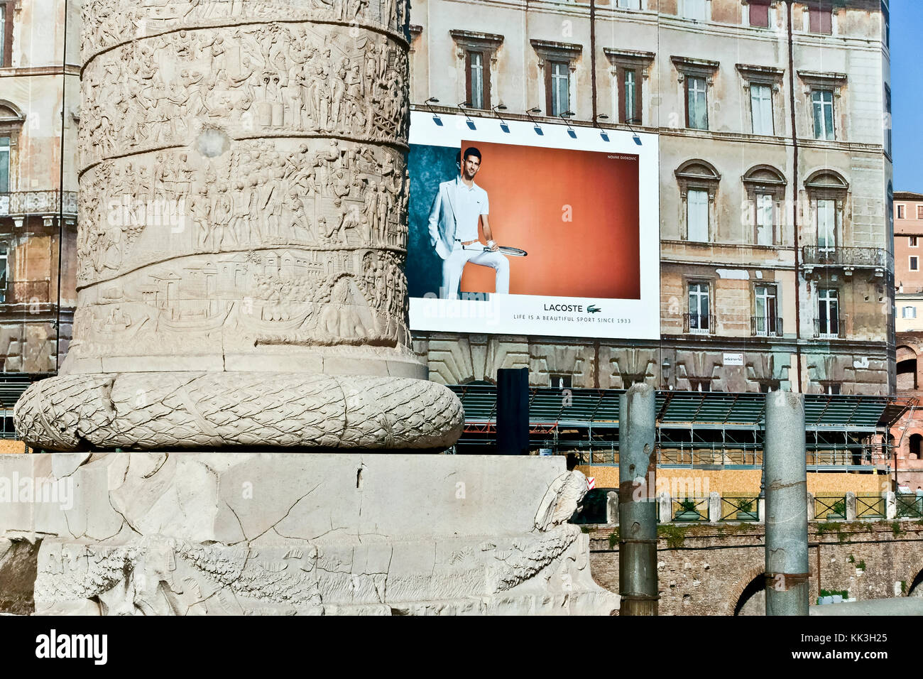 Lacoste advertising billboard on a building scaffolding at Trajan's Market Forum. Trajan's column close up. Rome, - Stock Image
