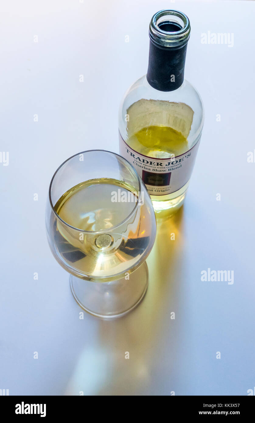 An open bottle and glass of Trader Joe's Charles Shaw Blend of Pinot Grigio -- three-buck chuck - Stock Image