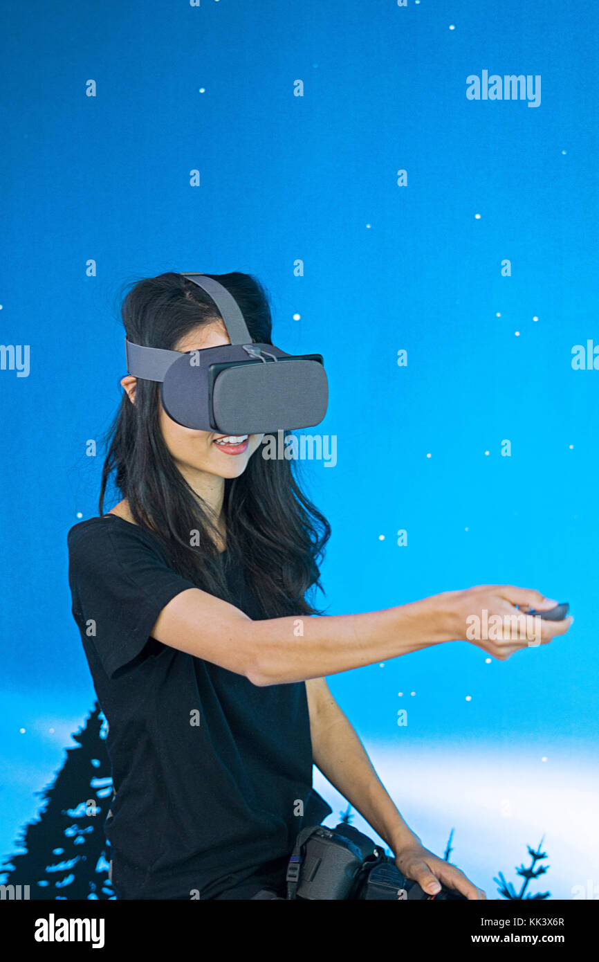 A young Asian lady testing a Google Daydream Virtual Reality headset inside the Google pop up store on Fifth Avenue - Stock Image