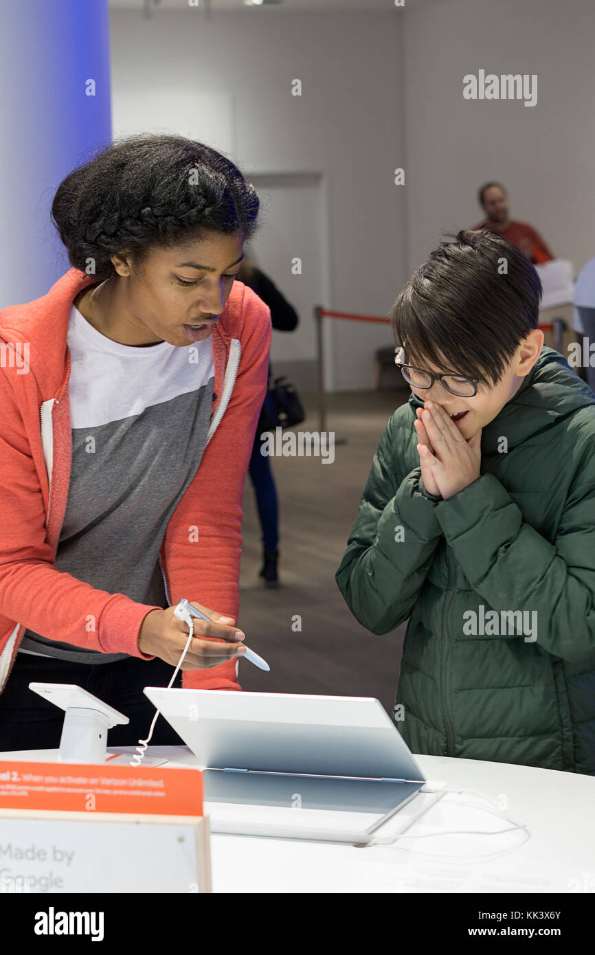 A staffer shows an excited Asian American boy new computer technology inside the Google pop up store on Fifth Avenue - Stock Image