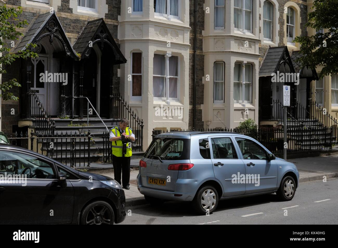 Traffic warden recording parking violation, Aberystwyth, Wales, UK - Stock Image