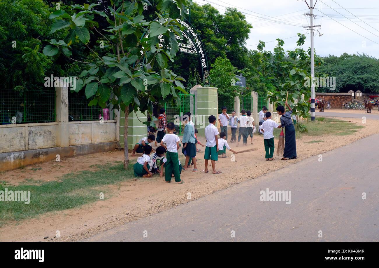 Children sweeping up outside school in Bagan, Myanmar - Stock Image