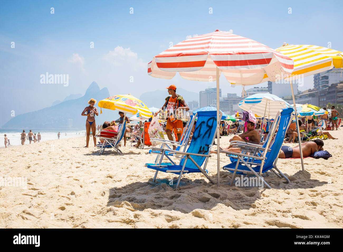 RIO DE JANEIRO - MARCH 06, 2016: A beach vendor selling South American mate iced tea and snacks walks in bright - Stock Image