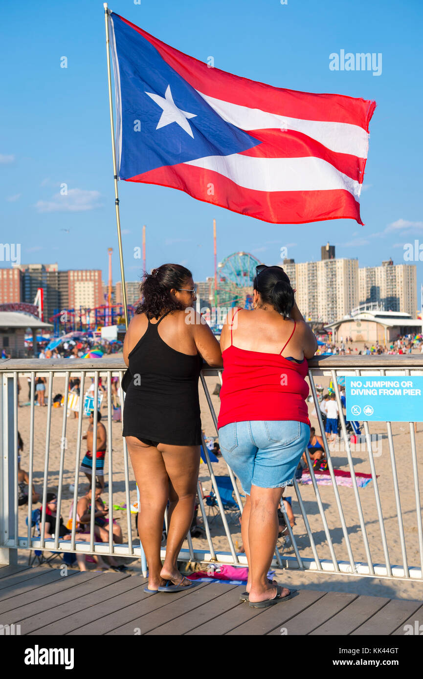 NEW YORK CITY - AUGUST 20, 2017:  A Puerto Rican flag waves above two women standing on the boardwalk overlooking - Stock Image