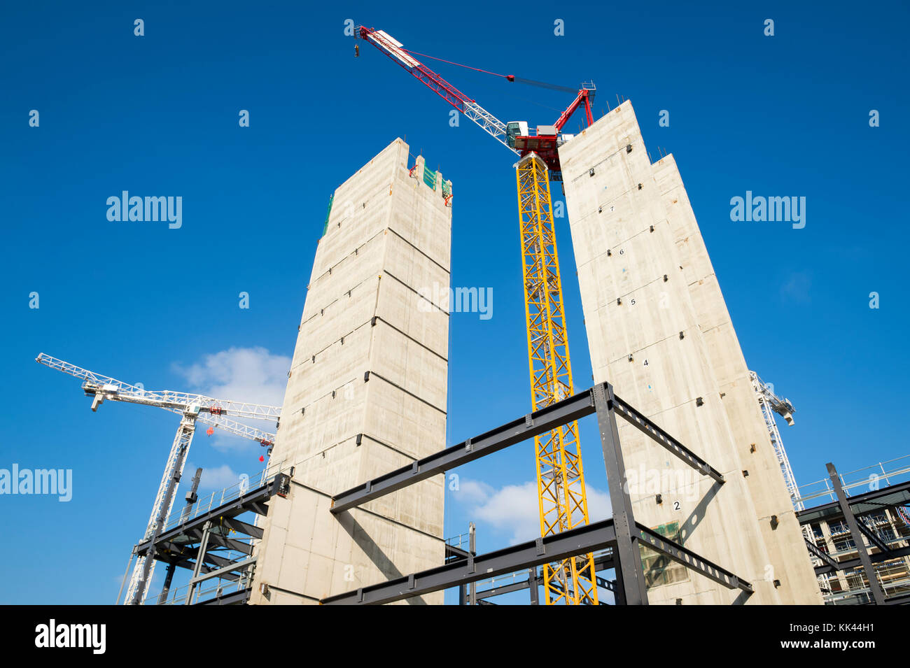Modern hi-rise towers construction site with cranes under bright blue sky - Stock Image