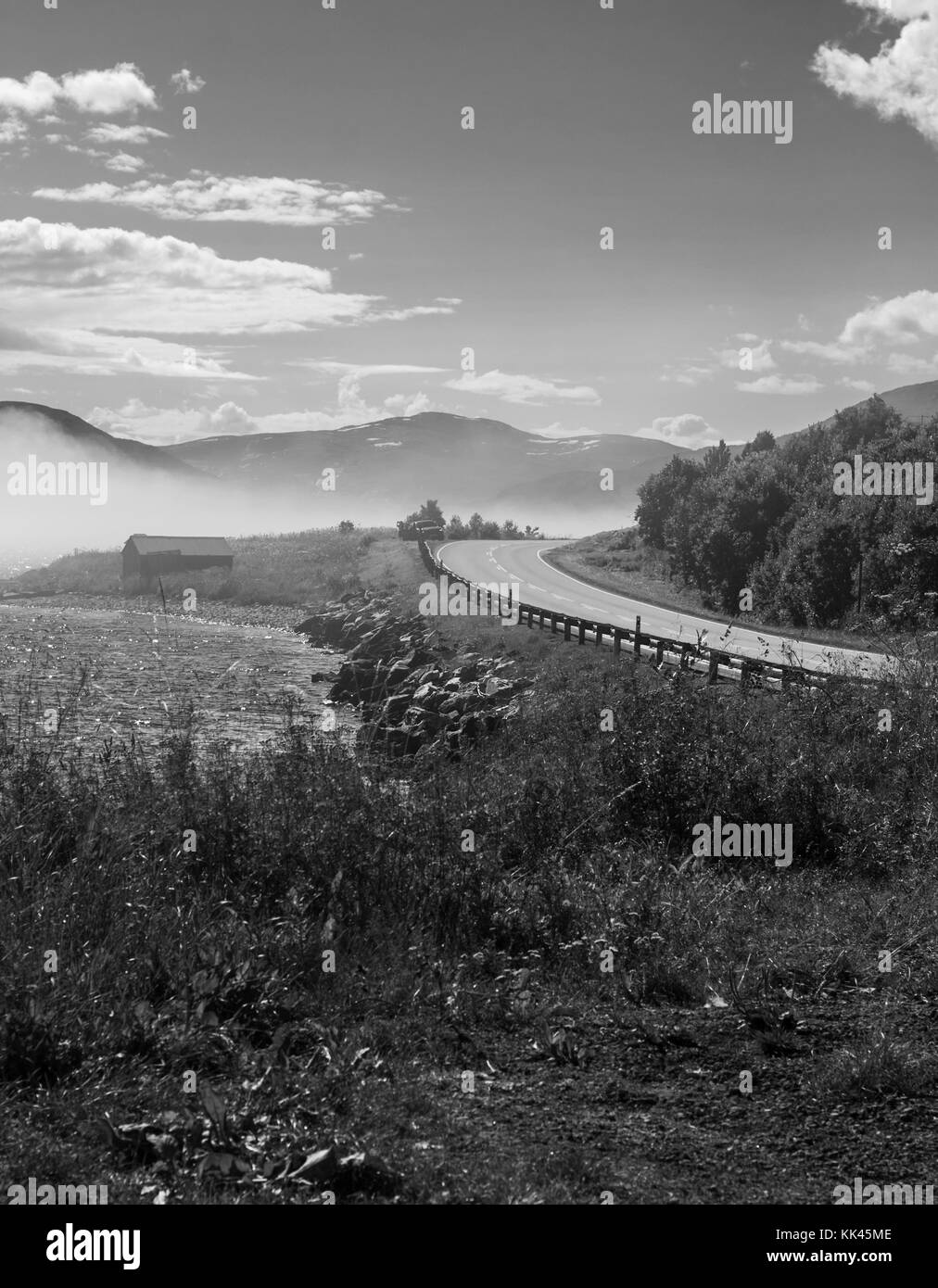 A steep curve of the road against the backdrop of mountains - Stock Image