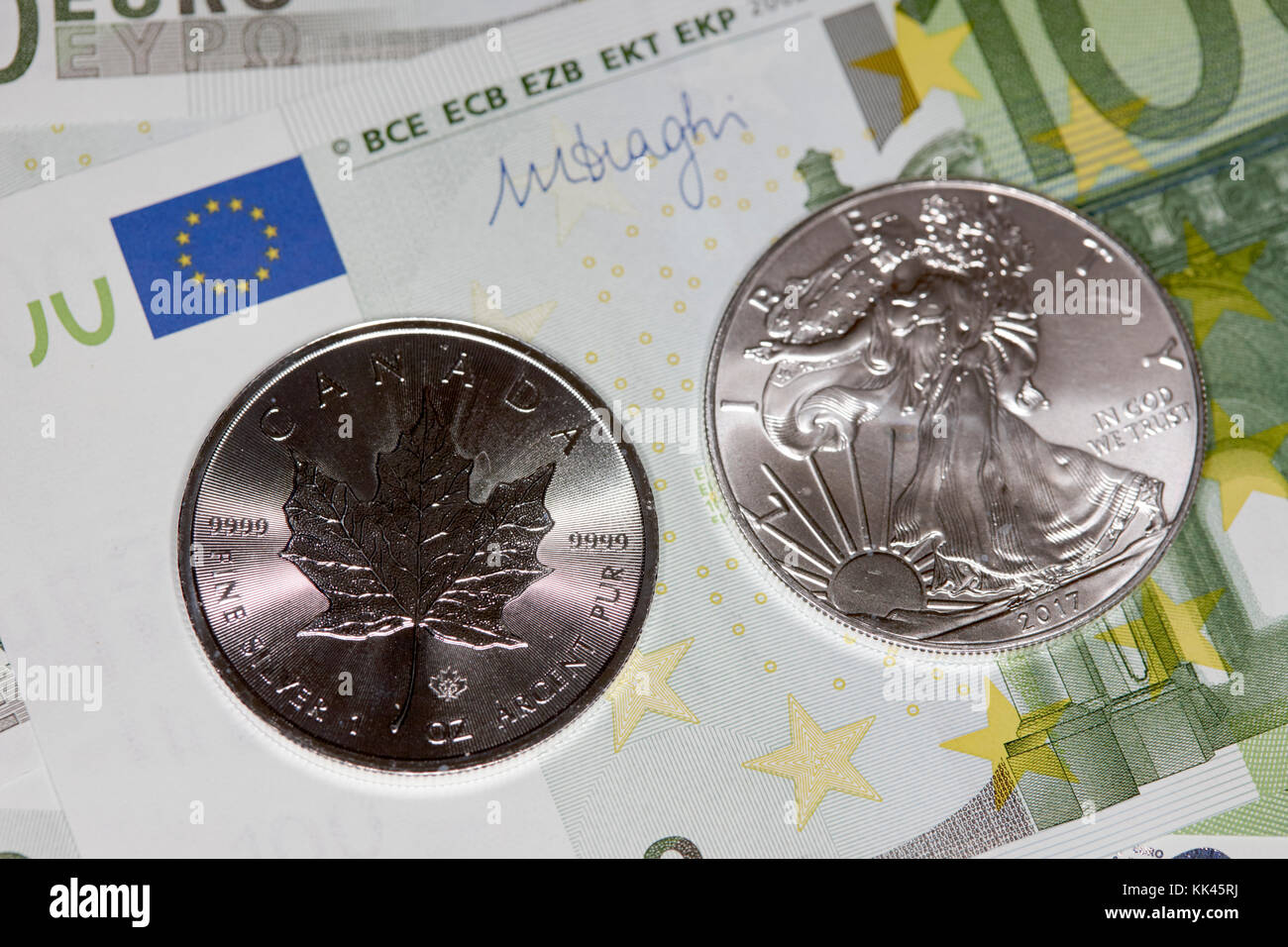 1oz silver bullion coins with euro banknotes - Stock Image