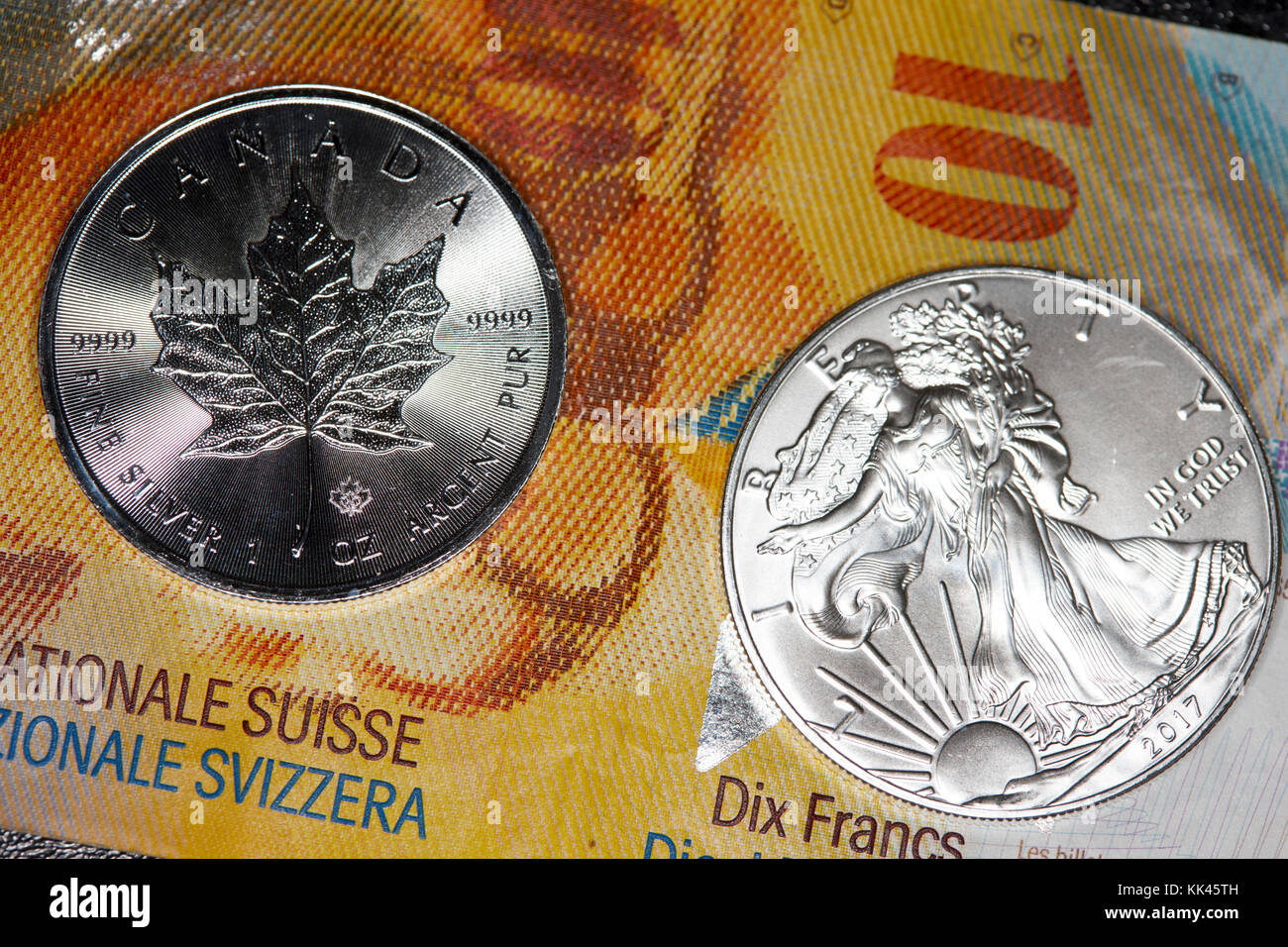 swiss franc banknotes with 1oz silver bullion coins - Stock Image
