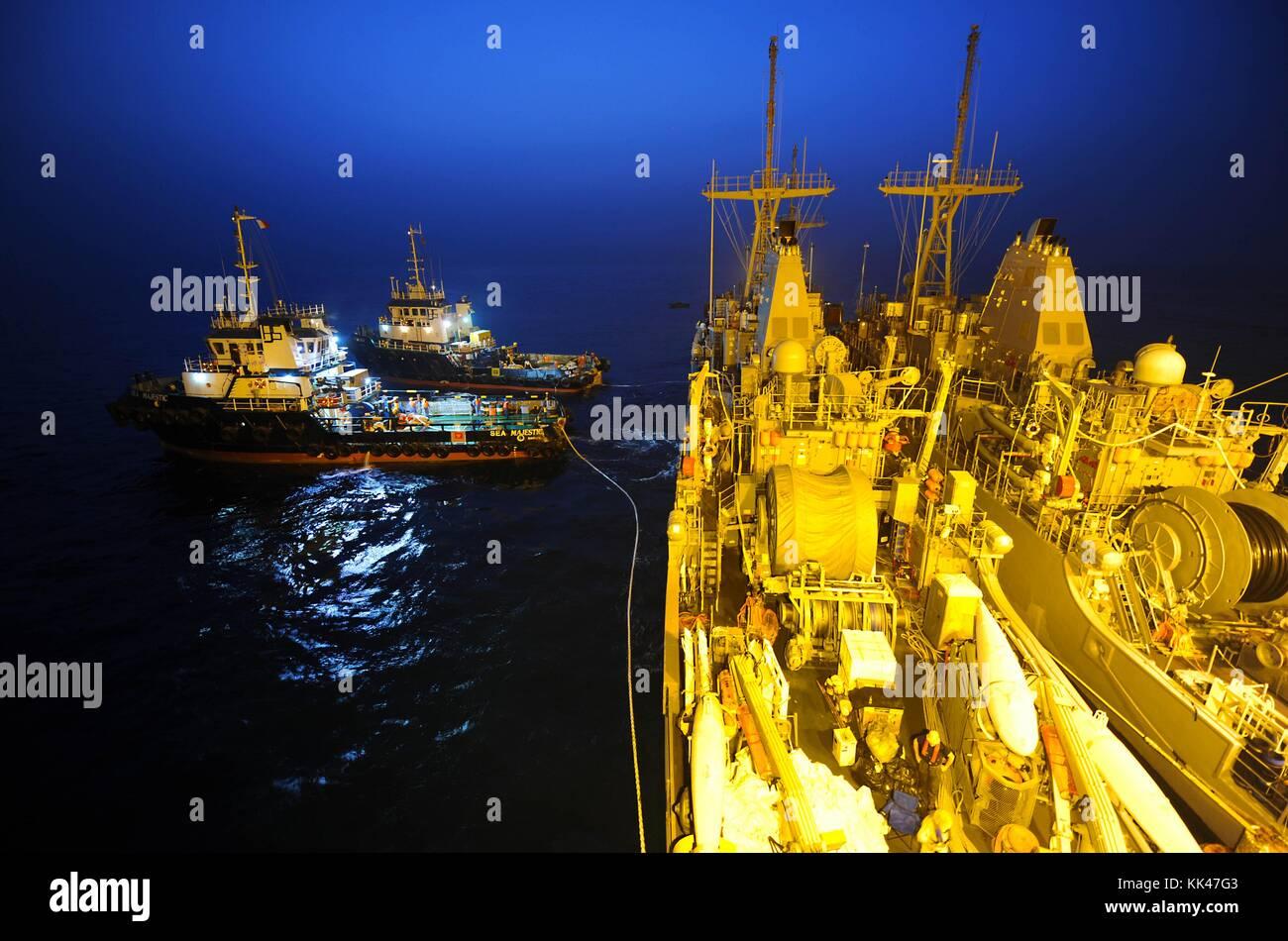 Tugboats pull the mine countermeasure ship USS Devastator MCM 6, left, off the Military Sealift Command chartered - Stock Image