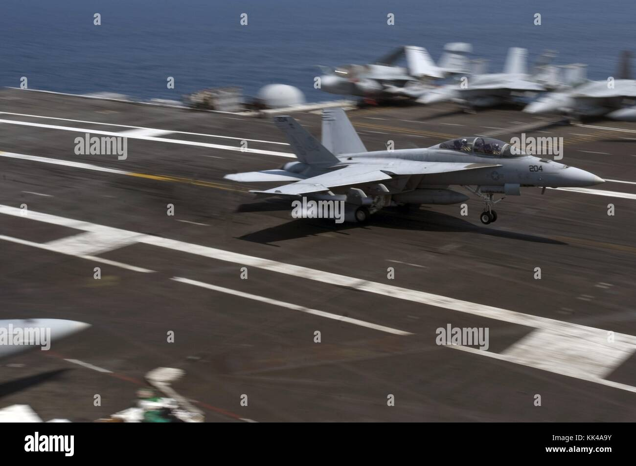 An F/A-18F Super Hornet assigned to the Jolly Rogers of Strike Fighter Squadron VFA 103 lands on the flight deck - Stock Image