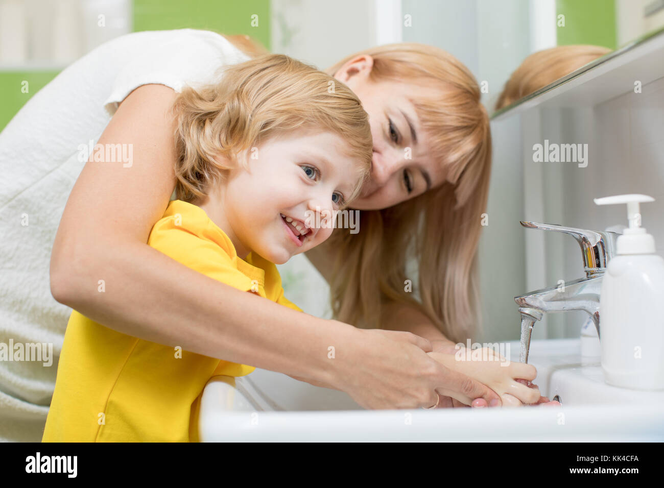 Mother and child son washing their hands in the bathroom. Care and concern for kids. - Stock Image