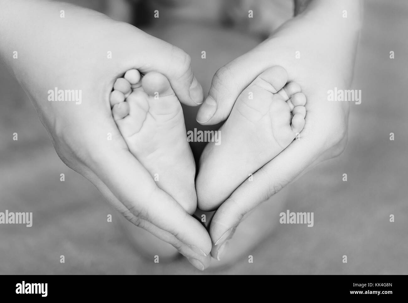 heels of newborn in mother hands forming a heart - Stock Image