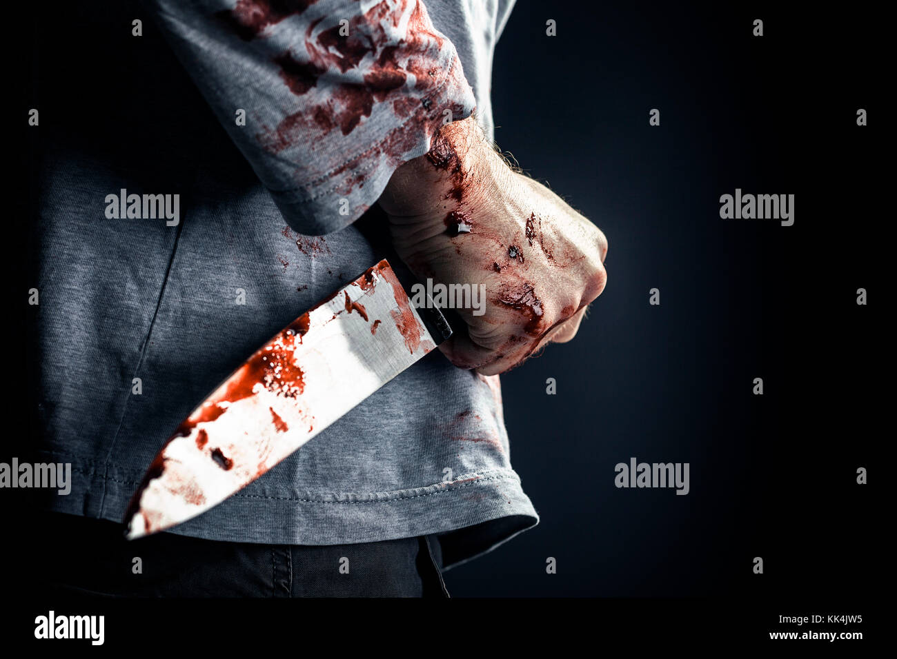 detail of man holding bloody knife crime concept - Stock Image