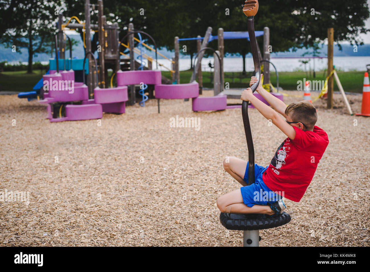 A boy child plays on playground equipment on a summer day - Stock Image
