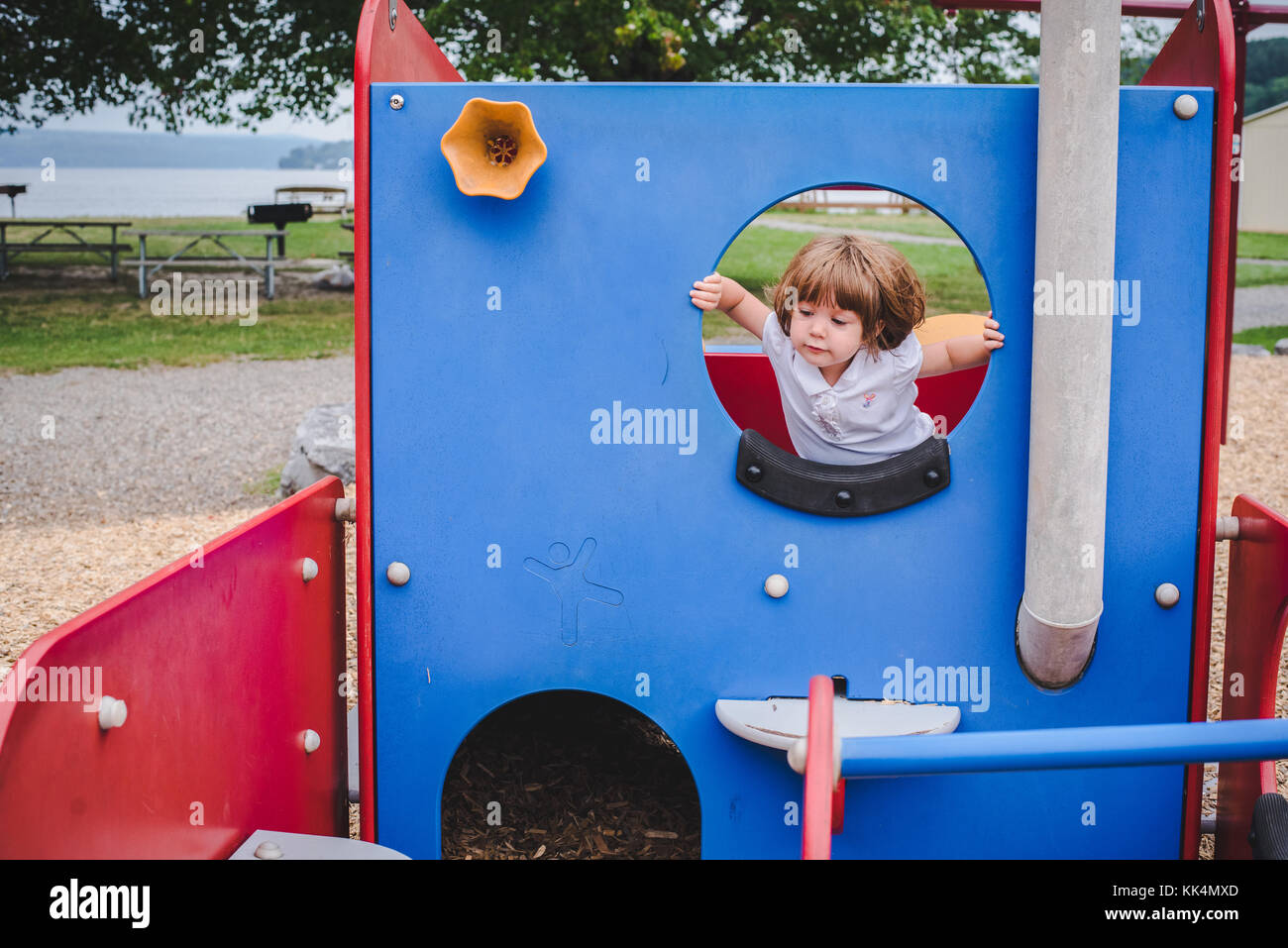 A little girl climbs on playground equipment on summer day - Stock Image