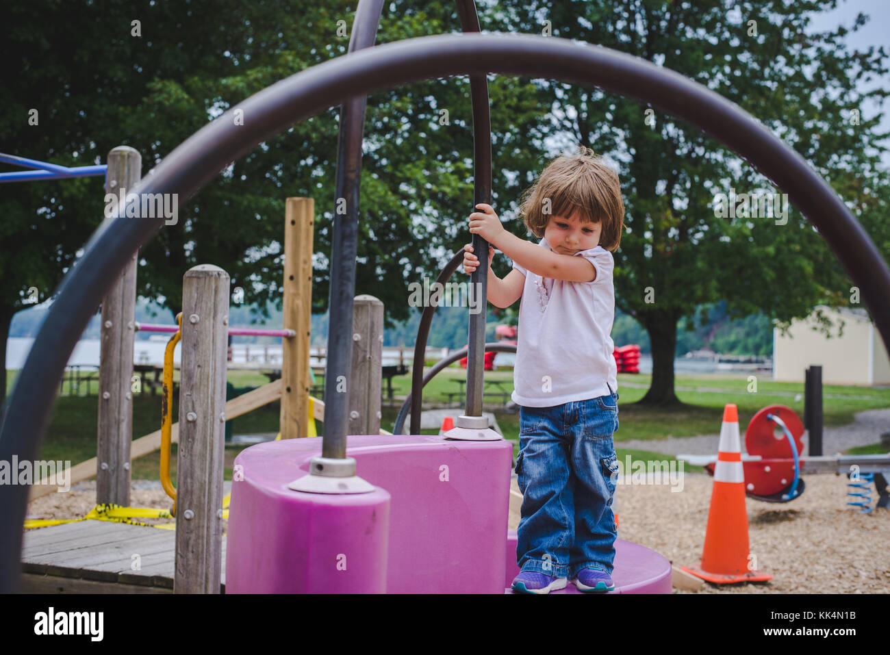 A little girl climbs on playground equipment on summer day Stock Photo