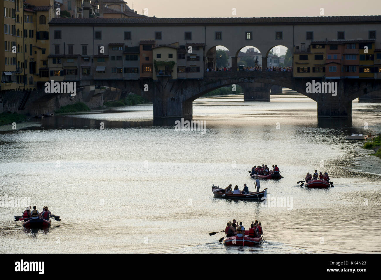 Leisure boat cruising on Arno river and Ponte Vecchio (Old Bridge) in Historic Centre of Firenze listed World Heritage - Stock Image