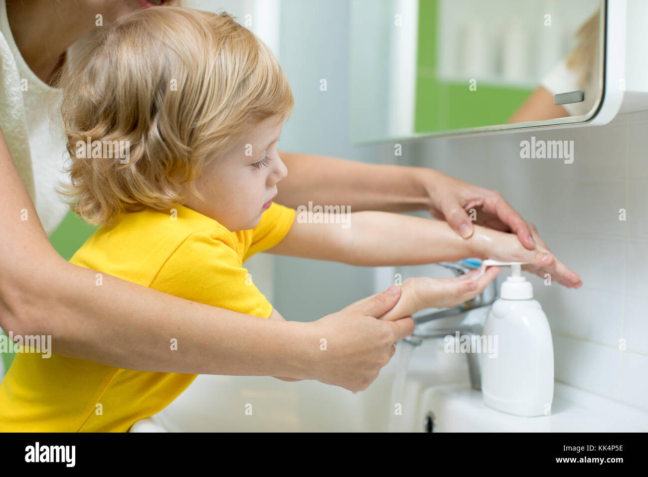Mother and kid son washing their hands in the bathroom. Care and concern for children. - Stock Image