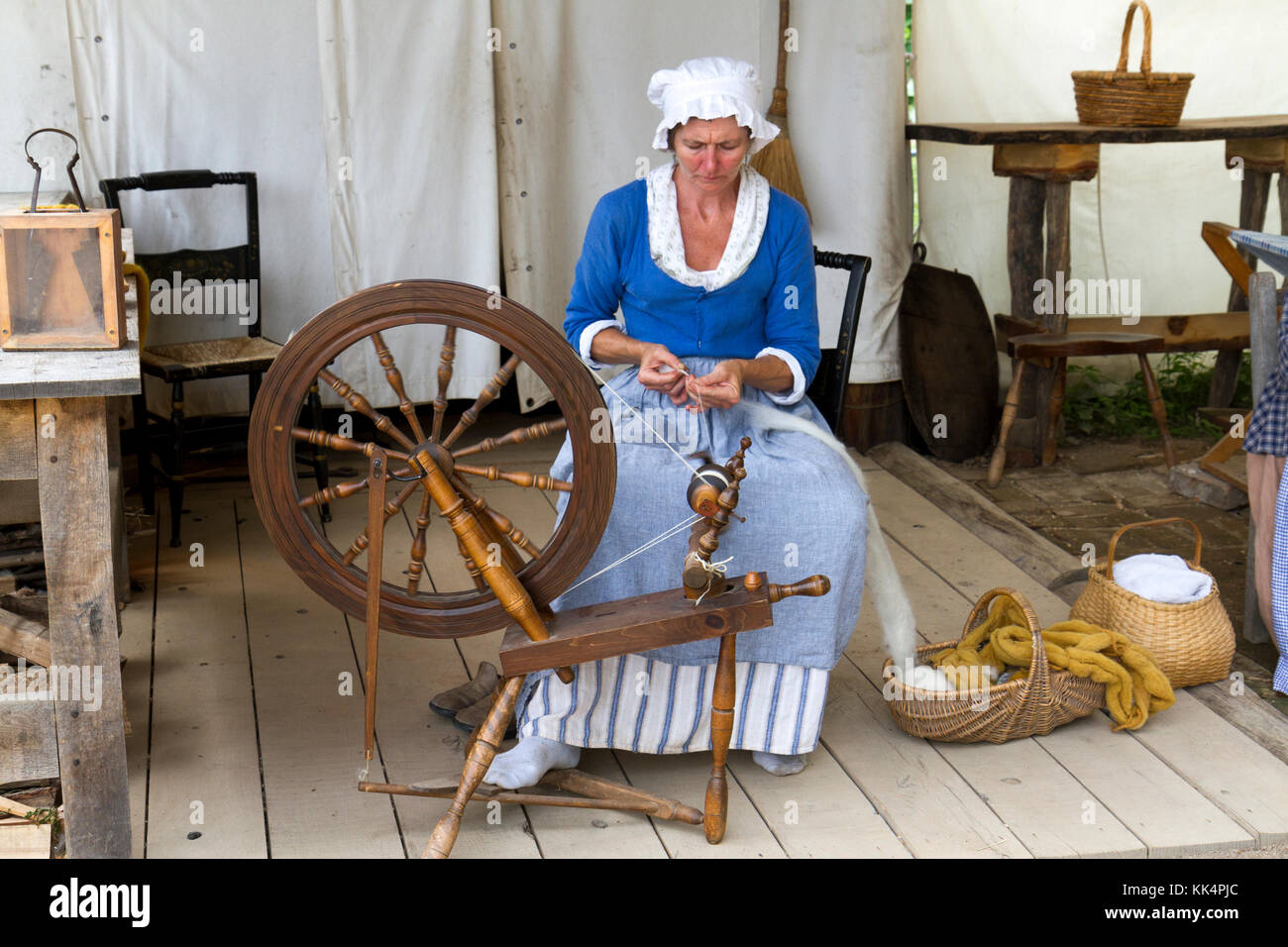 Close up of a woman making yarn from wool on a foot operated spinning wheel on the Mount Vernon estate, Virginia, - Stock Image