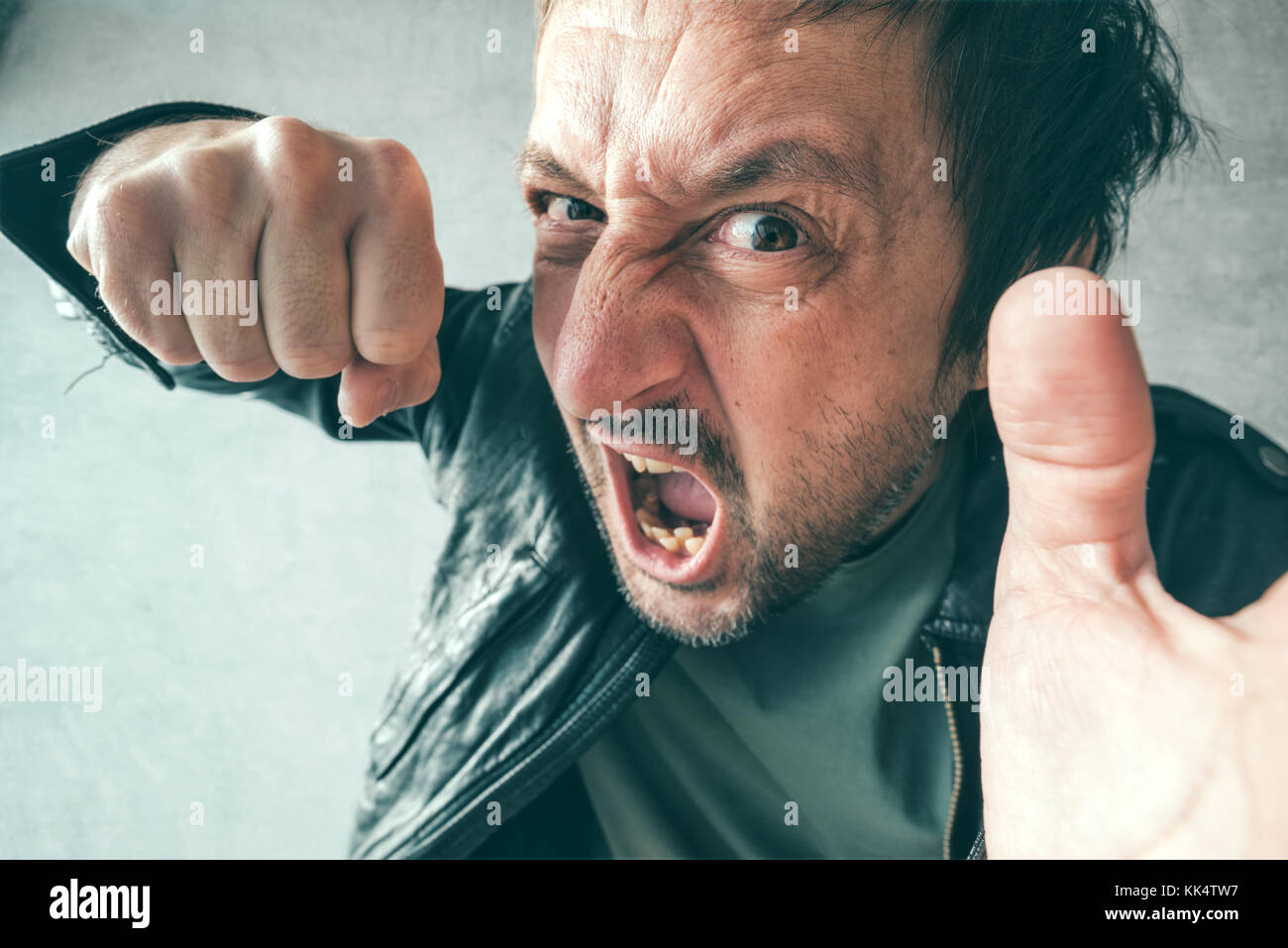 Aggressive man punching with fist during the fight, from victim's point of view. Violence and crime concept. - Stock Image