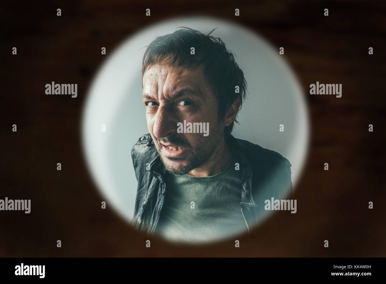 Angry man at the door viewed through spy hole, debt collector or criminal knocking at the door - Stock Image