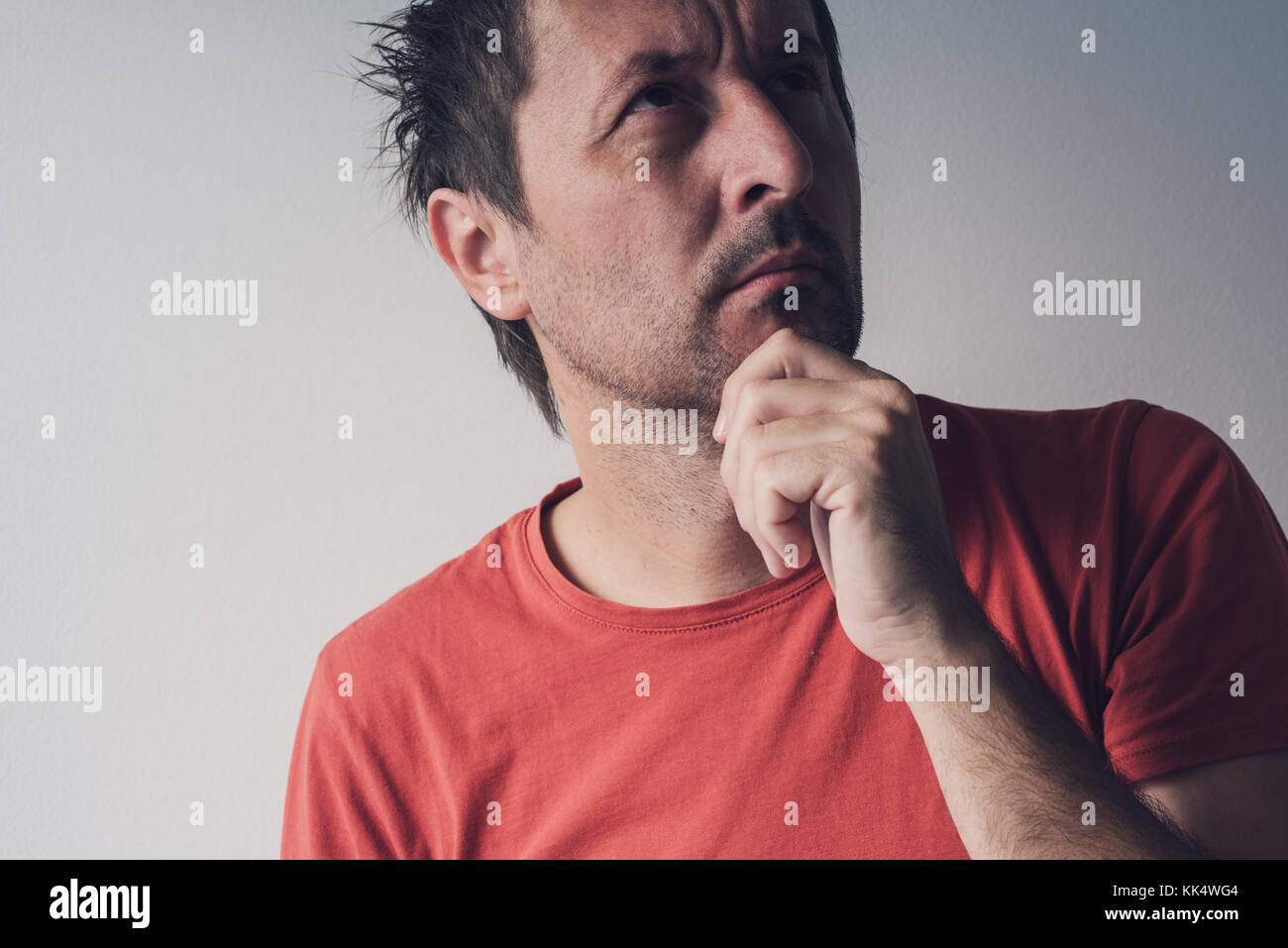 Serious portrait of adult caucasian man looking up and thinking, real people facial expressions - Stock Image