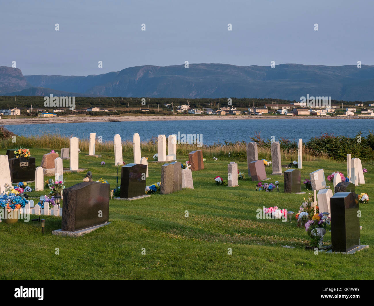 Anglican Cemetery with town in the background, Cow Head village, Gros Morne National Park, Newfoundland, Canada. - Stock Image