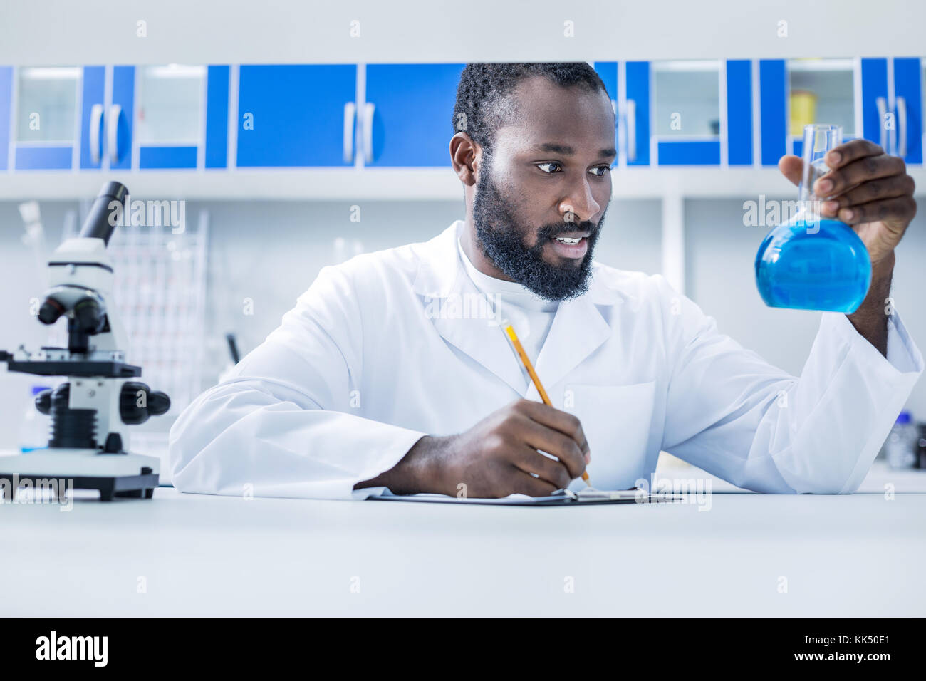 Serious professional chemist taking notes - Stock Image