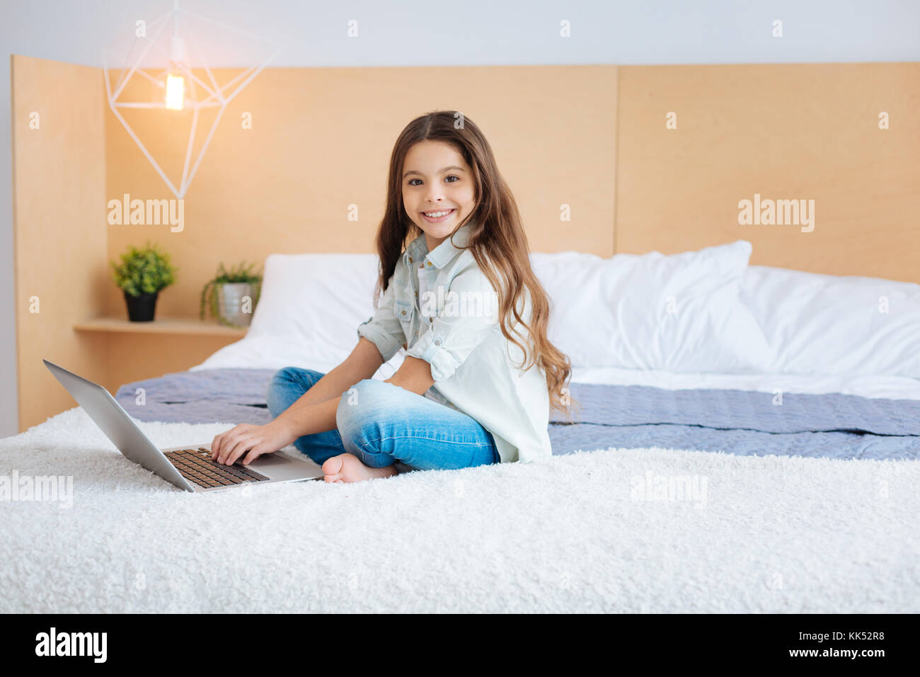 Time spending. Cheerful confident optimistic girl spending her leisure with a laptop  recreating in the bedroom - Stock Image