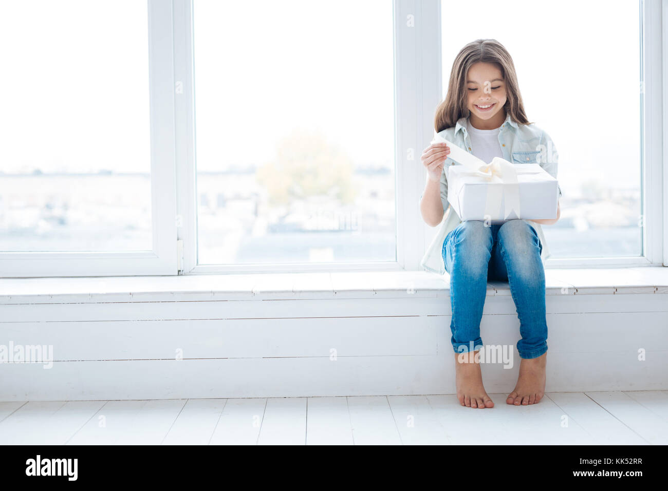 Great present. Window sill becomes recreating place for happy attractive little girl  who unpacking her present - Stock Image