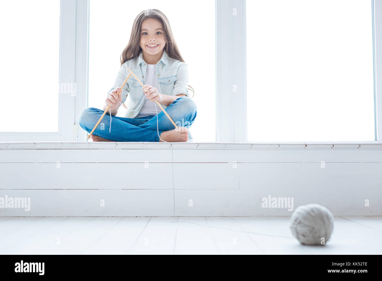 Knitting sweater. Sweet good looking kind girl sitting on the window sill and holding knitting needled while grey - Stock Image