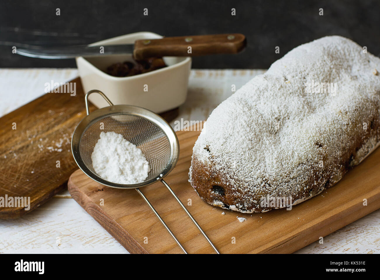 Homemade Whole Christmas Stollen on Wood Cutting Board Sieve with Powder Knife Ingredients Rustic Kitchen Interior - Stock Image