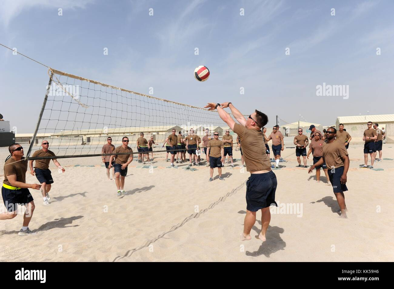 Seabees assigned to Naval Mobile Construction Battalion NMCB 11 play a friendly game of volleyball at Camp Leatherneck - Stock Image