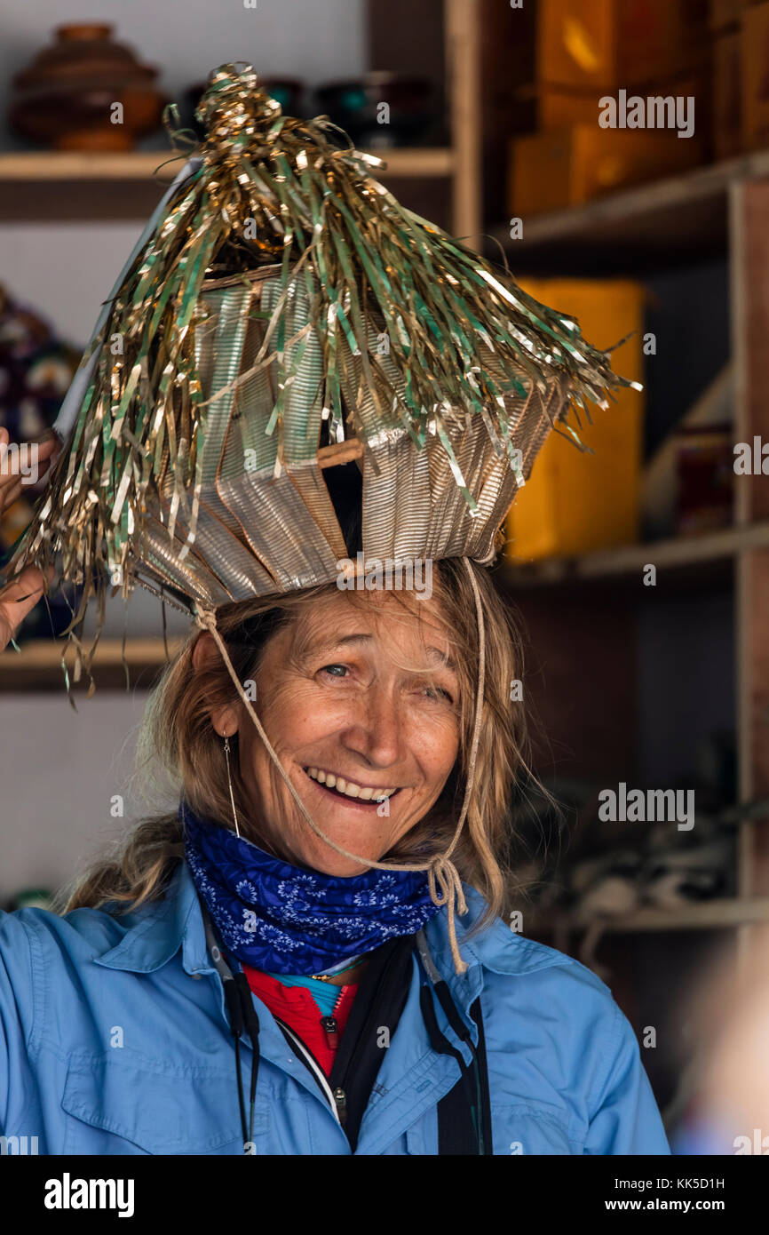 CARROLL DUNHAM wears a funny hat in a shop at LAMAYURU - LADAKH, INDIA - Stock Image