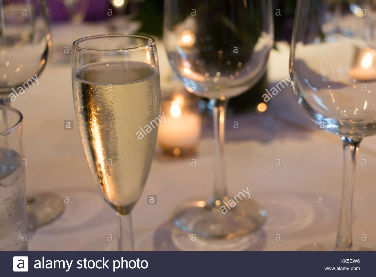 Champagne flute illuminated by candle light. - Stock Image