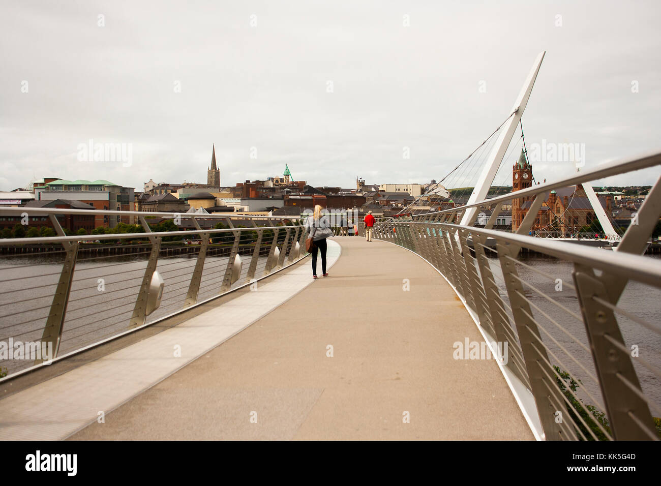 Pedestrians crossing the iconic Peace Bridge over the river Foyle in Londonderry City in Northern Ireland - Stock Image