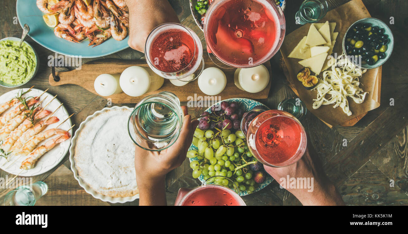 Flat-lay of friends hands eating and drinking together, wide composition - Stock Image