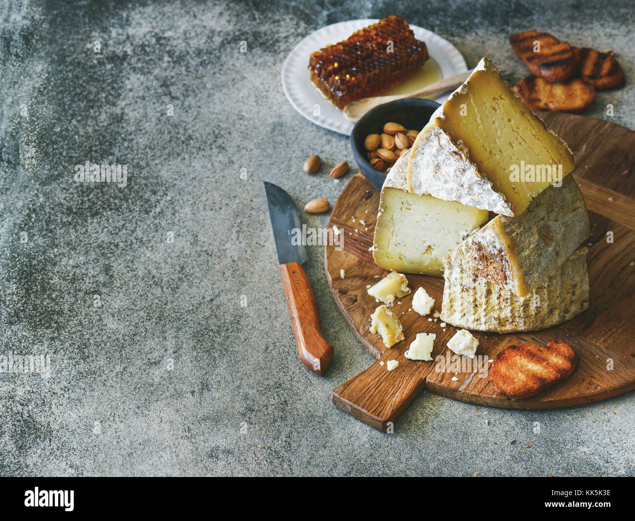 Cheese assortment and snacks on rustic wooden board, copy space - Stock Image