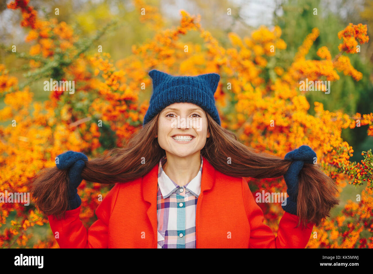 Model wearing stylish winter beanie hat and gloves smiling - Stock Image